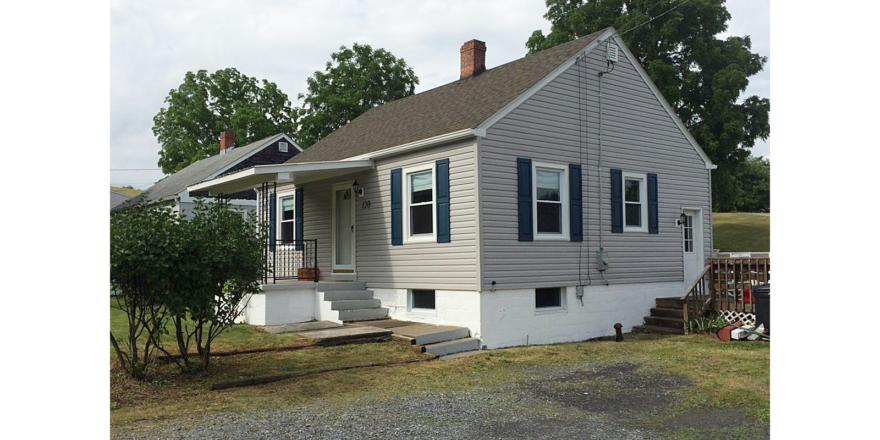 Exterior of building with gray siding and dark blue shutters.
