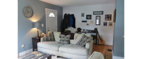 Living room and entryway with couch, loveseat, pictures and tables
