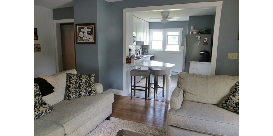 Kitchen with white cabinets and counter top, stainless steel appliances and living room with couch and loveseat