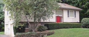 Exterior of house with tan siding, red front door, lawn, and landscaping