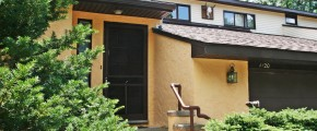 Exterior of duplex with large garage and yellow stucco siding