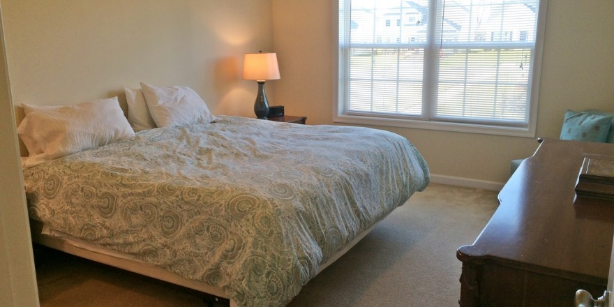 Carpeted bedroom with queen bed, dresser, chair, nightstand with lamp, and large window