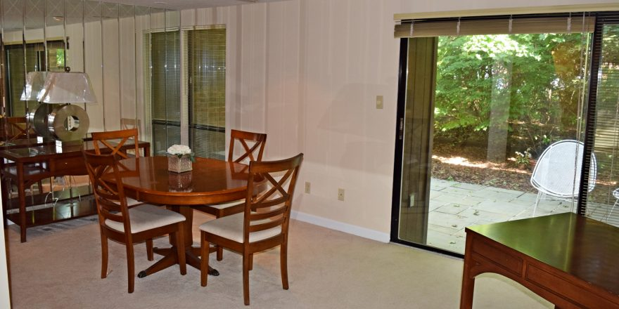 Dining room with oval table and four chairs, large mirrored wall and large sliding glass door onto a patio