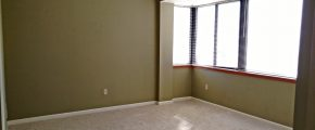Unfurnished, carpeted bedroom with large windows