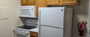 Kitchen with fridge, washing machine and microwave