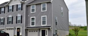 Exterior of townhouse with gray siding, black front door, with a one car garage and driveway