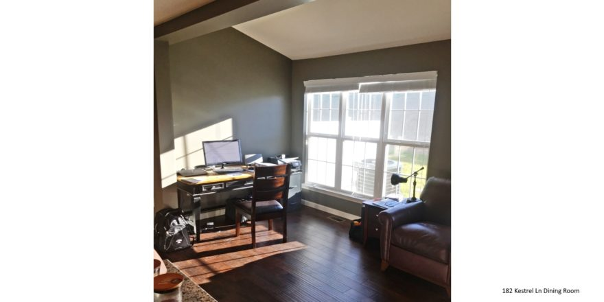 Living room with wood-style flooring, leather armchair, desk with computer and large window