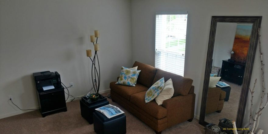 Living room with love seat, window, large mirror, two small accent tables, and decor