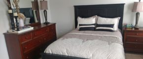 Carpeted bedroom with queen bed, wood dresser with seven drawers, mirror, and nightstand