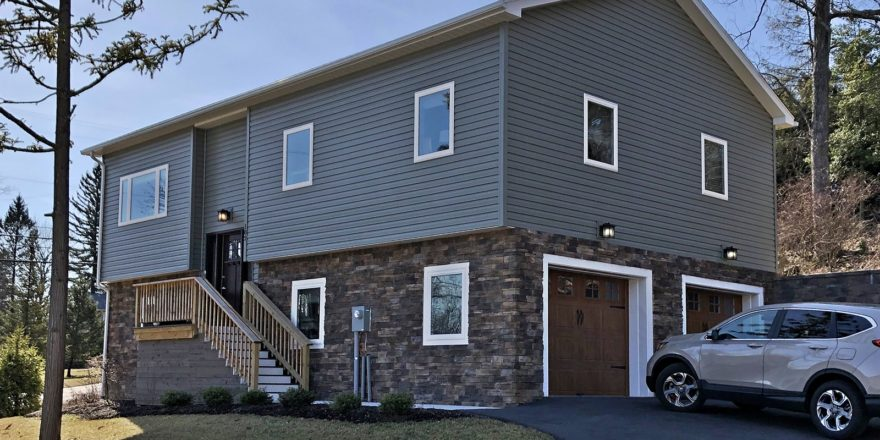 House with gray siding and stone siding. Stairs lead up to the front door and there are two garage doors on the side.