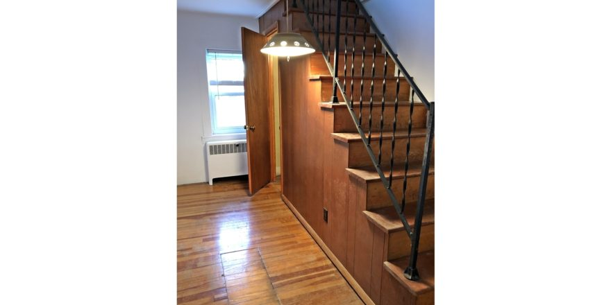 Wooden stair case with hanging light and hardwood floor.