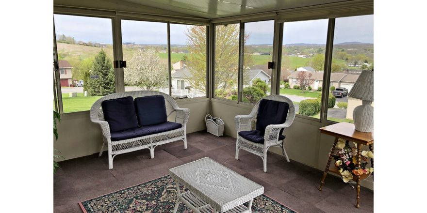 Sunporch with wicker furniture, rug, end table, and large windows