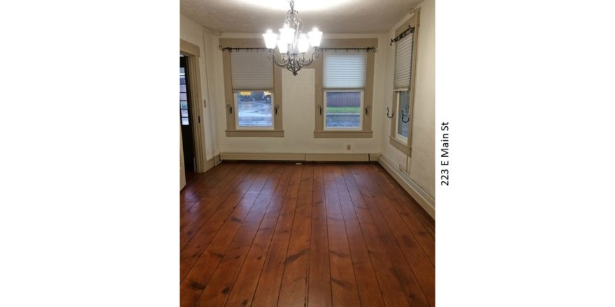 Unfurnished dining room with windows, chandelier, and hardwood floors