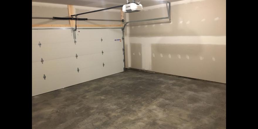 Empty garage with large door and cement floor