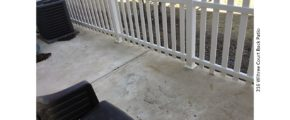 Concrete patio with white picket fence