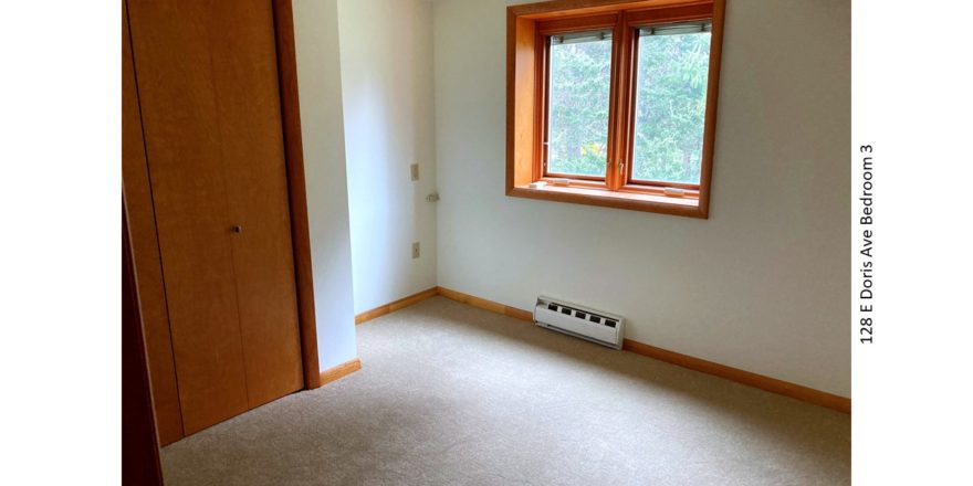 Unfurnished and carpeted bedroom with closet and crank windows