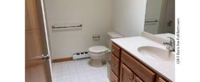 Bathroom with tile floor, toilet and large vanity and mirror