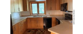 Kitchen with black appliances, parkay flooring, and light wood cabinets