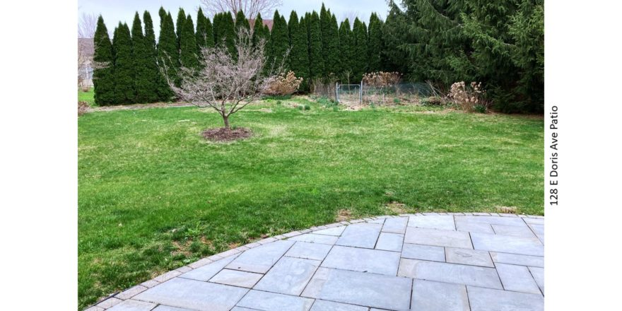 Back yard with lawn, small fenced in garden and patio