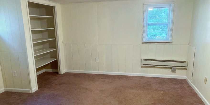 Unfurnished, carpeted bedroom with built in shelving