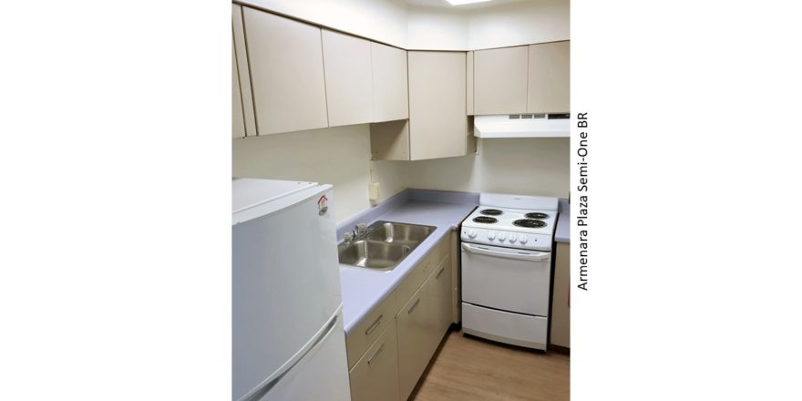 Kitchen with double sink, refrigerator, and range oven